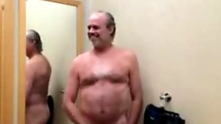 A naked daddy in a clothing store fitting room masturbating and cumming.